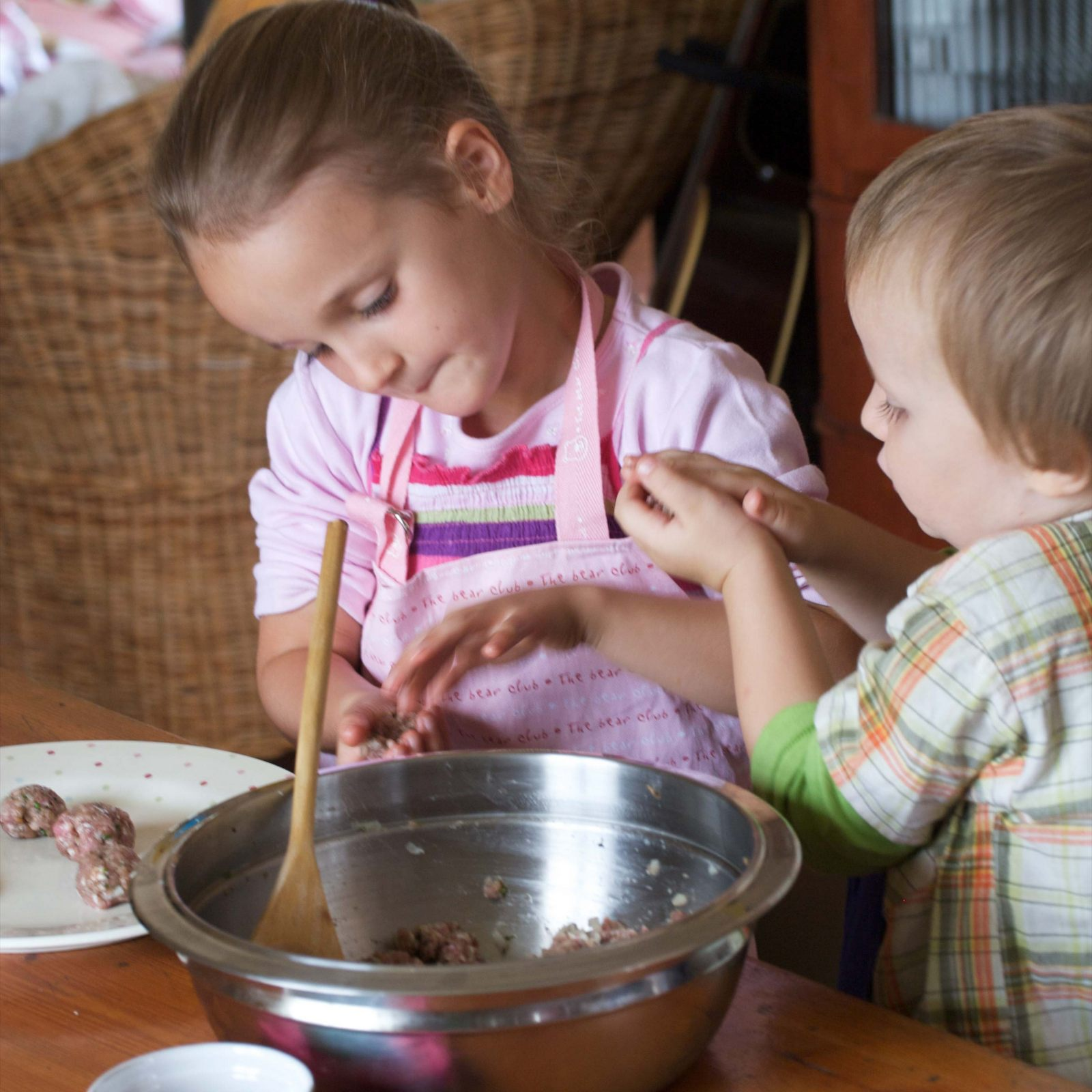 Kids making meatballs with tomato sauce