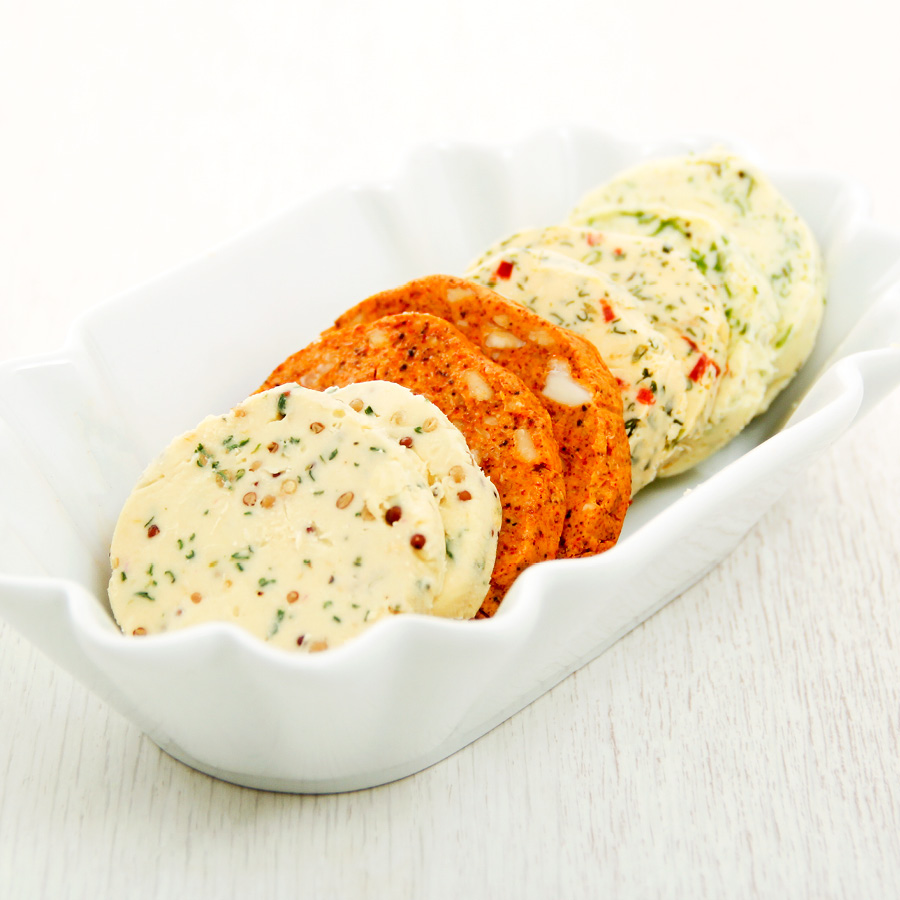 Savoury flavoured butters in a white dish