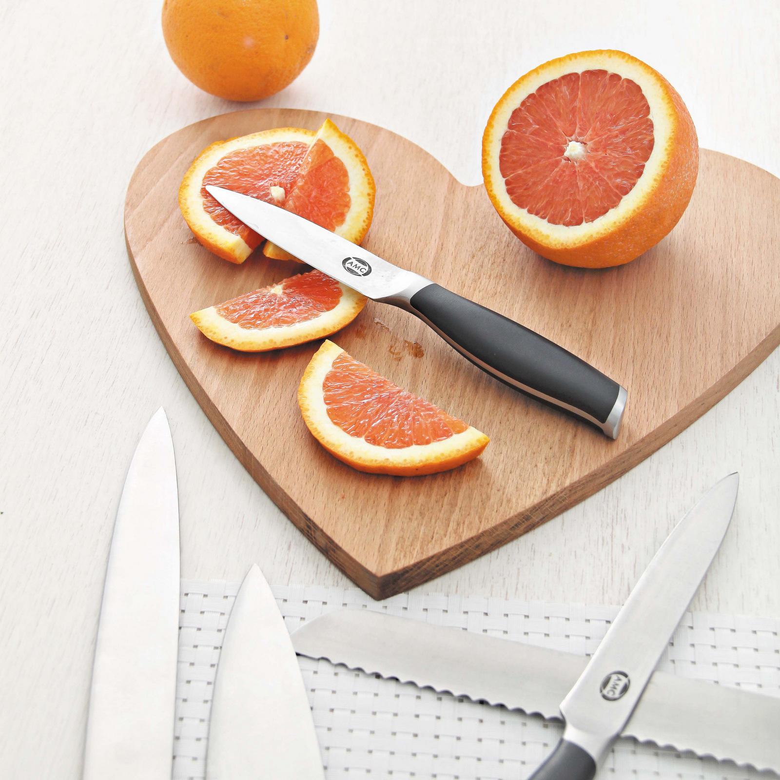 AMC Edge knives on cutting board with sliced orange.